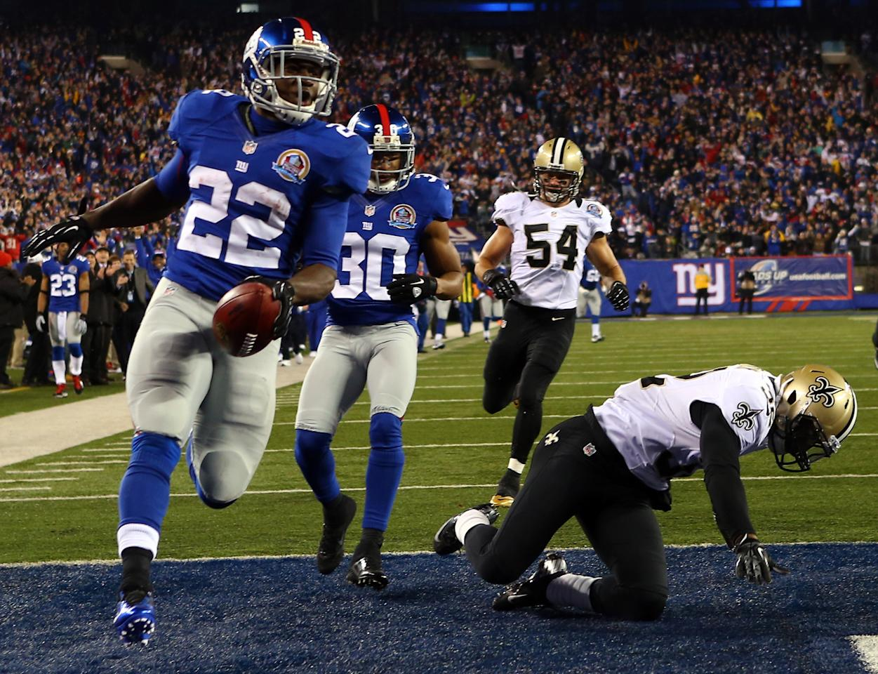 EAST RUTHERFORD, NJ - DECEMBER 09:   David Wilson #22 of the New York Giants celebrates his touchdown while Johnny Patrick #32 of the New Orleans Saints falls on December 9, 2012 at MetLife Stadium in East Rutherford, New Jersey.  (Photo by Elsa/Getty Images)