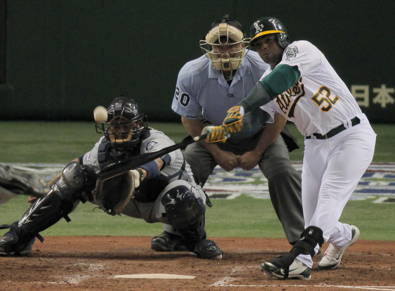 Oakland Athletics' Yoenis Cespedes hits a double as Seattle Mariners catcher Miguel Olivo looks on in the seventh inning of their American League season opening MLB baseball game at Tokyo Dome in Tokyo, Wednesday, March 28, 2012. (AP Photo/Itsuo Inouye)