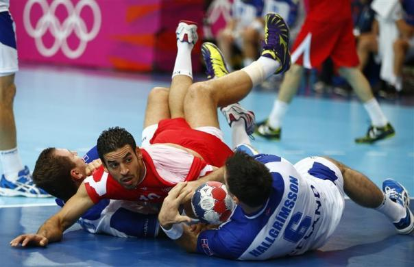 Tunisia's Kamel Alouini (C) falls to the ground after colliding with Iceland's Sverre Jakobsson (L) and Asgeir Orn Hallgrimsson in their men's handball Preliminaries Group A match at the Copper Box venue during the London 2012 Olympic Games July 31, 2012.
