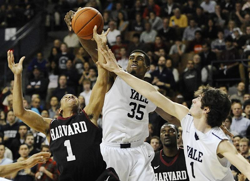 Yale's Brandon Sherrod, center, fouls Harvard's Siyani Chambers, left, as Yale's Anthony Dallier, right, defends during the second half of an NCAA college basketball game, Friday, March 7, 2014, in New Haven, Conn. Harvard won 70-58