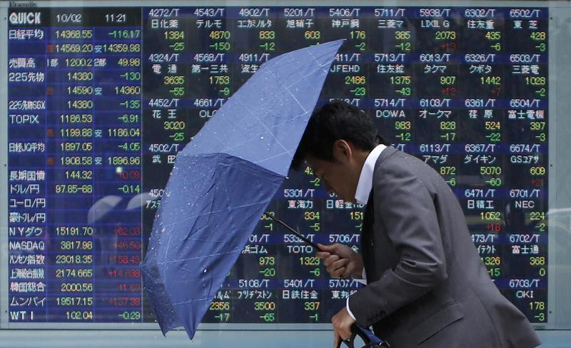 A man walks against strong wind and rain in front of a stock quotation board outside a brokerage in Tokyo