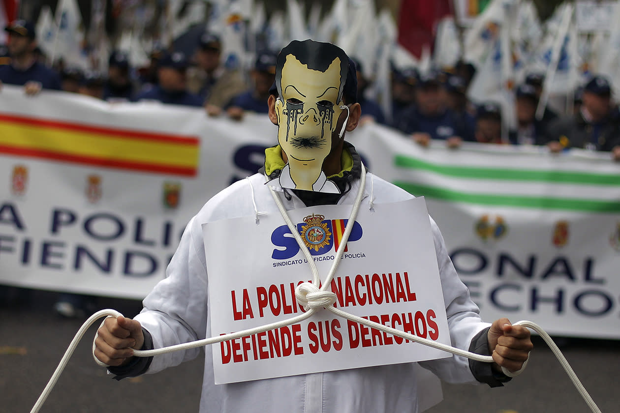 "A police officer marches carrying a banner reading, ""National police fights for its rights"" during a protest  against the government's austerity measures and the elimination of their Christmas bonus pay, one of 14 paychecks that most Spanish civil servants get each year, in Madrid."