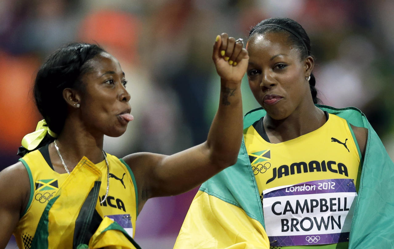 Jamaica's Shelly-Ann Fraser-Pryce sticks out her tongue as she celebrates winning the gold with bronze winner, Jamaica's Veronica Campbell-Brown, during the athletics competition in the Olympic Stadium at the 2012 Summer Olympics, Saturday, Aug. 4, 2012, in London. (AP Photo/Marcio Sanchez)