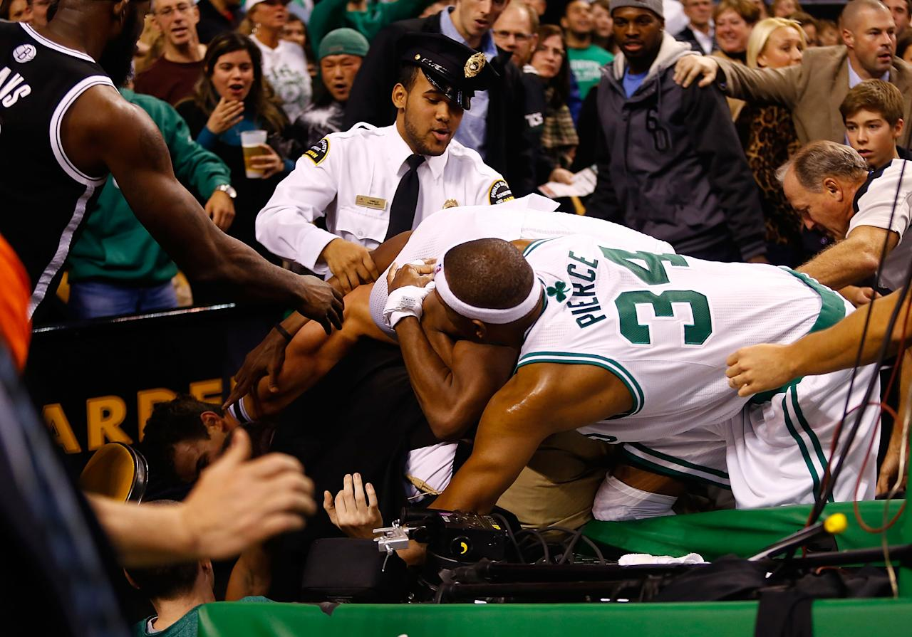 BOSTON, MA - NOVEMBER 28: Paul Pierce #34 and Rajon Rondo #9 of the Boston Celtics fight with Kris Humphries #43 of the Brooklyn Nets while security and referees attempt to break it up behind the basket after Humphries fouled Kevin Garnett #5 of the Boston Celtics during the game on November 28, 2012 at TD Garden in Boston, Massachusetts. Kris Humphries and Rajon Rondo would be immediately ejected from the game. NOTE TO USER: User expressly acknowledges and agrees that, by downloading and or using this photograph, User is consenting to the terms and conditions of the Getty Images License Agreement.  (Photo by Jared Wickerham/Getty Images)