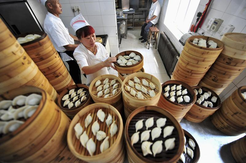 A cook arranges baskets of newly-made dumplings at a restaurant in Shenyang