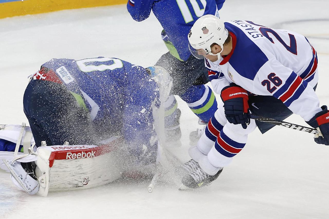 Slovenia goaltender Luka Gracnar dives on the puck in front of USA forward Paul Stastny during the 2014 Winter Olympics men's ice hockey game at Shayba Arena Sunday, Feb. 16, 2014, in Sochi, Russia. (AP Photo/Petr David Josek)