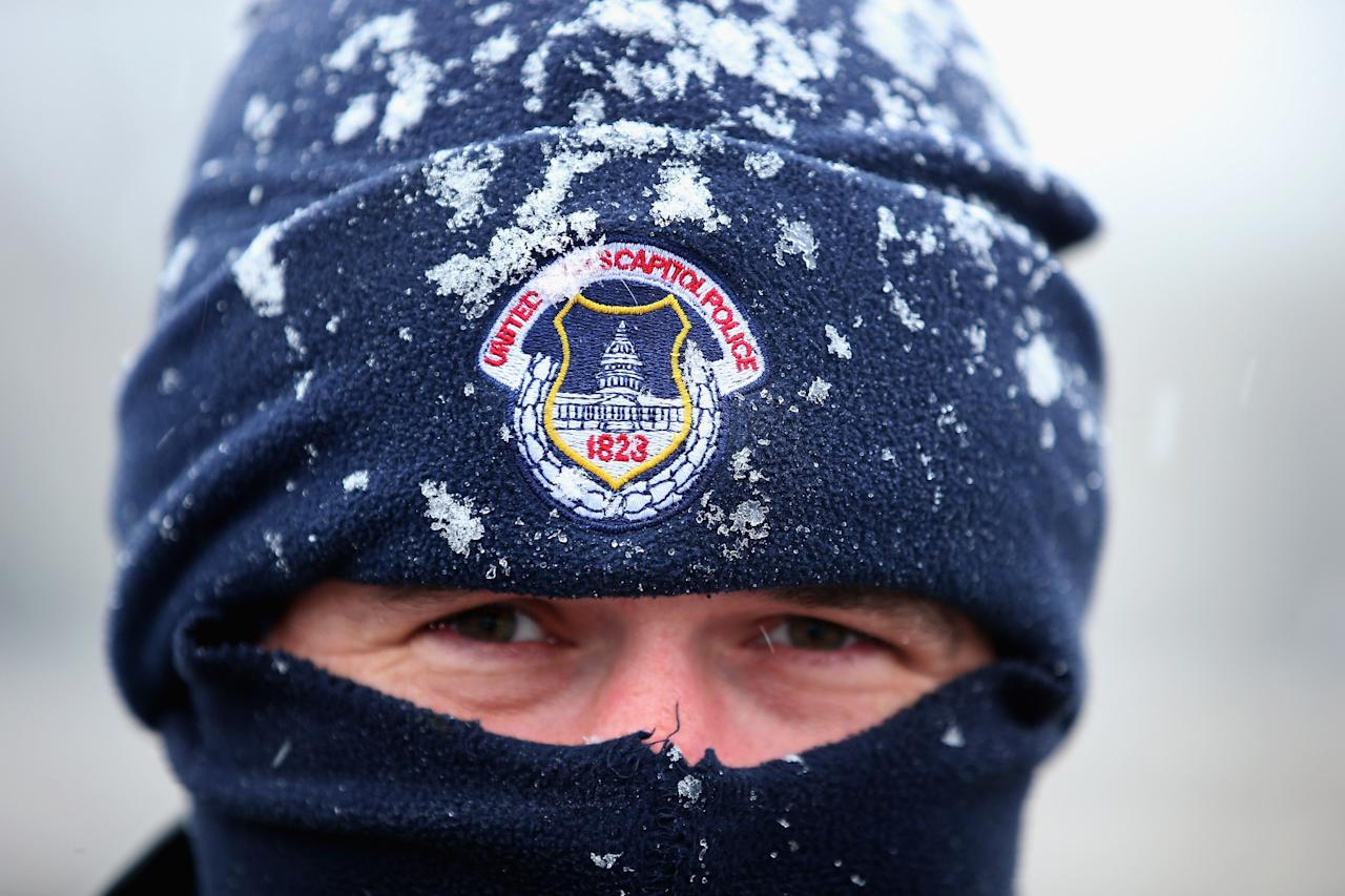 WASHINGTON, DC - MARCH 06:  U.S. Capitol Police officer Alex Rys' hat is dusted with snow as he patrols on Capitol Hill March 6, 2013 in Washington, DC. A late winter storm is expected to cover the Mid-Atlantic region after dropping almost a foot of snow across the the West and Midwest.  (Photo by Chip Somodevilla/Getty Images)