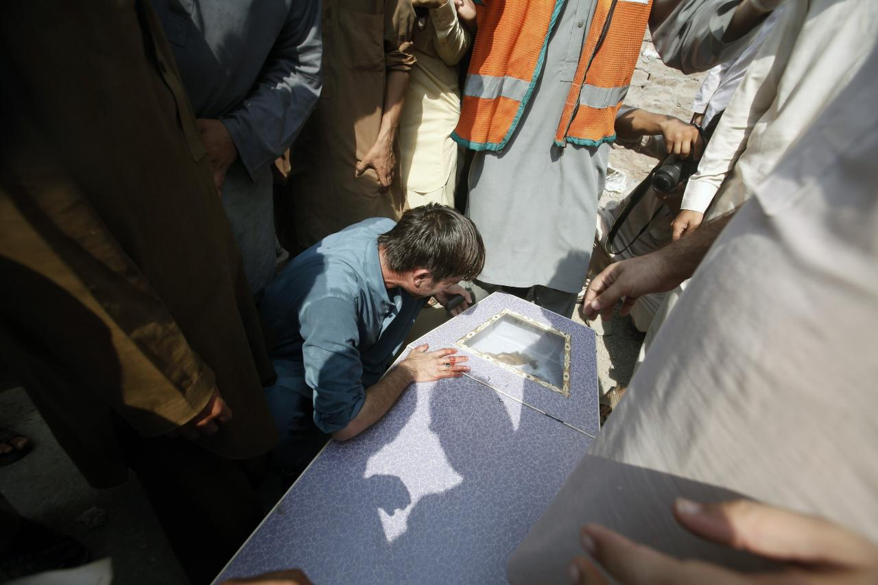 A man cries over the coffin of his brother, who was killed in a bomb blast, at a hospital in Peshawar September 29, 2013. Twin blasts in the northwestern Pakistan city of Peshawar killed 33 people and wounded 70 on Sunday, a week after two bombings at a church in the frontier city killed scores, police and hospital authorities said.REUTERS/ Fayaz Aziz (PAKISTAN - Tags: POLITICS CIVIL UNREST CRIME LAW)
