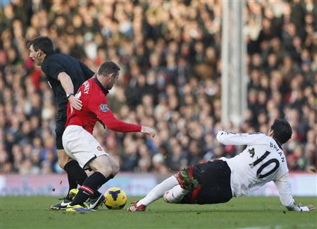 Manchester United's Rooney collides with referee Probert as he is challenged by Fulham's Ruiz during their English Premier League soccer match at Craven Cottage in London