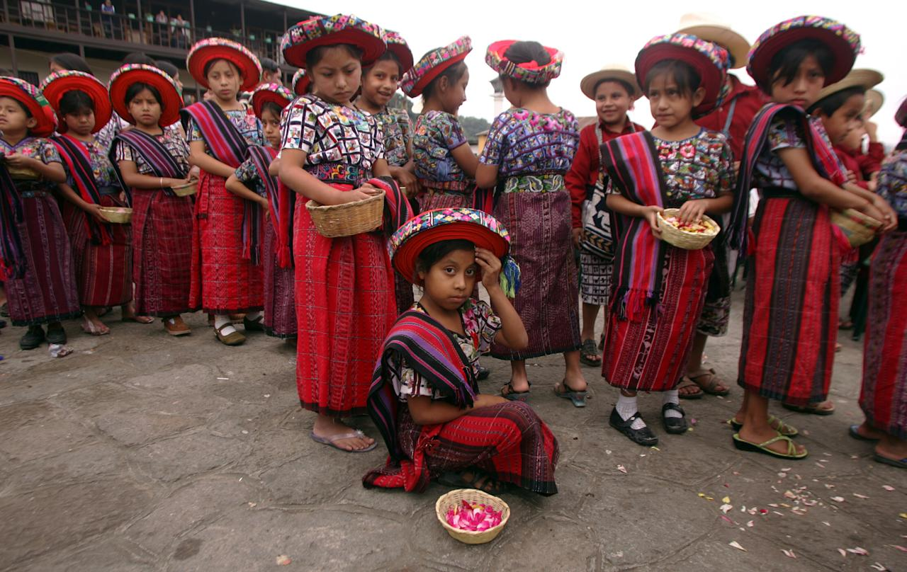 Indigenous Mayan children prepare for a memorial service in honor of Father Stanley Rother in the small town of Santiago Atitlan, Guatemala July 28, 2006. Rother was an Oaklahoman priest killed 25 years ago on July 28 for his work with the poor during Guatemala's brutal civil war. REUTERS/Daniel LeClair  (GUATEMALA)