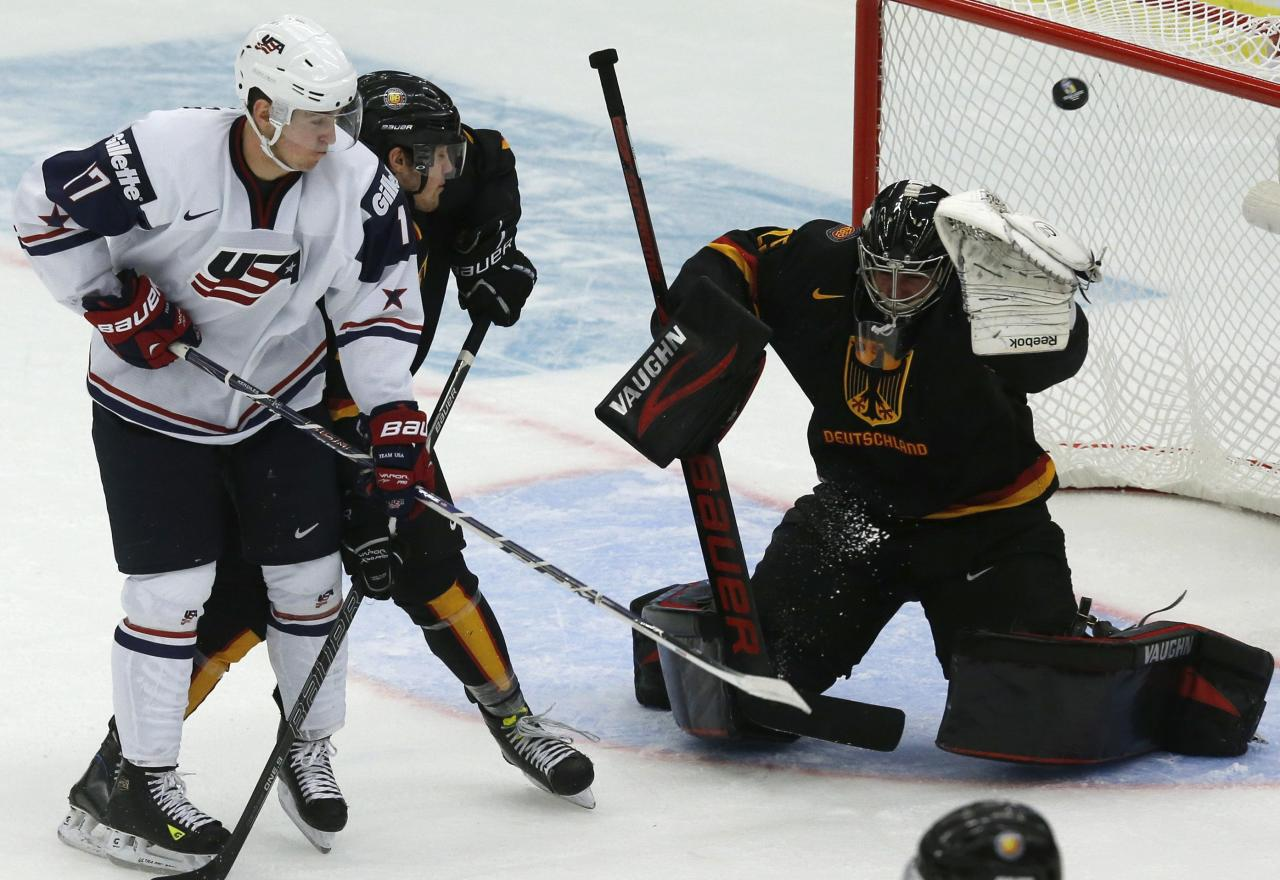 Nikolas Kerdiles (L) of the U.S. tries to score past Germany's goalie Anthony Stolarz (R) and Matt Grzelcyk during the second period of their IIHF World Junior Championship ice hockey game in Malmo, Sweden, December 29, 2013. REUTERS/Alexander Demianchuk (SWEDEN - Tags: SPORT ICE HOCKEY)