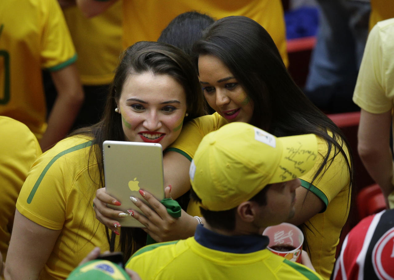 Two Brazil supporters pose for a photo ahead of the group A World Cup soccer match between Cameroon and Brazil at the Estadio Nacional in Brasilia, Brazil, Monday, June 23, 2014. (AP Photo/Christophe Ena)