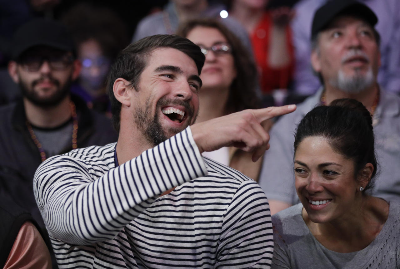 FILE - In this March 21, 2017, file photo, Michael Phelps and his wife, Nicole Johnson, smile during an NBA basketball game between the Los Angeles Lakers and the Los Angeles Clippers in Los Angeles. If Phelps returns to competitive swimming, the demands of training would surely cut heavily into his family time. That's why, if he tries to predict what the future might hold, it doesn't include a sixth Olympics at Tokyo in 2020. (AP Photo/Jae C. Hong, File)