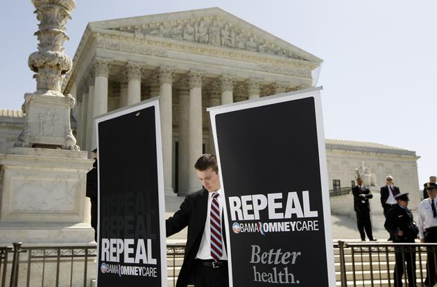 A campaign aide for Republican presidential candidate Rick Santorum, sets up signs in front of the Supreme Court.