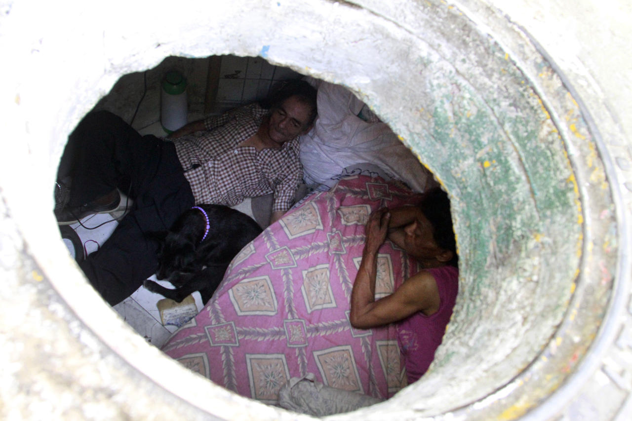 Miguel Restrepo (L), 62, and wife Maria Garcia are seen from their sewer home in Medellin December 4, 2012. The former drug addict has been living in an abandoned sewer with his wife and dog Blackie for 22 years. Their home, which is fitted with a kitchen, a fan, tv, a chair and a bed, is a 6 square meter wide and 1.4 meters high tunnel that leaks when it rains, and requires a manhole cover. REUTERS/Albeiro Lopera (COLOMBIA - Tags: SOCIETY POVERTY) - RTR3B7PH