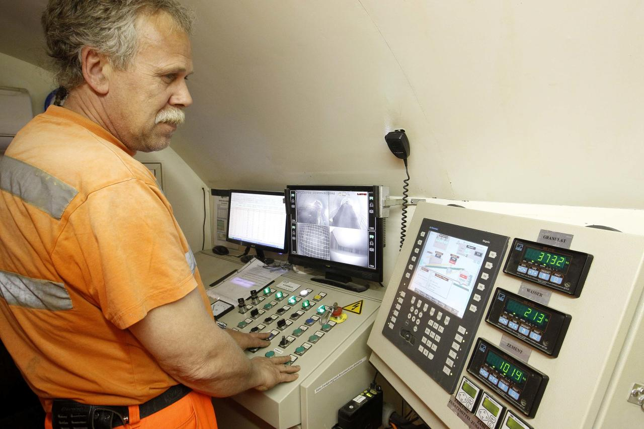 An employee looks at monitors to control the mixture of concrete on the special train 'Helvetia' in the NEAT Gotthard Base tunnel near Erstfeld May 7, 2012. The train, which is 481 metres (1578 ft) long and weighs 787 tons, is constructed to produce concrete for the installation of the railway tracks in the tunnel. Crossing the Alps, the world's longest train tunnel should become operational at the end of 2016. The project consists of two parallel single track tunnels, each of a length of 57 km (35 miles) REUTERS/Arnd Wiegmann   (SWITZERLAND - Tags: BUSINESS CONSTRUCTION EMPLOYMENT TRAVEL)
