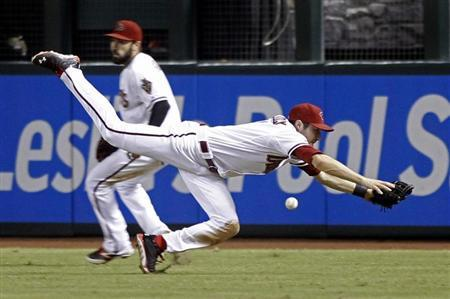 Arizona Diamondbacks center fielder Pollock dives but cannot make the catch of a ball hit by Los Angeles Dodgers' Young during their MLB National League baseball game in Phoenix