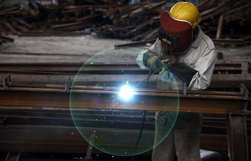 Worker welds at a machinery manufacturing factory in Huaibei
