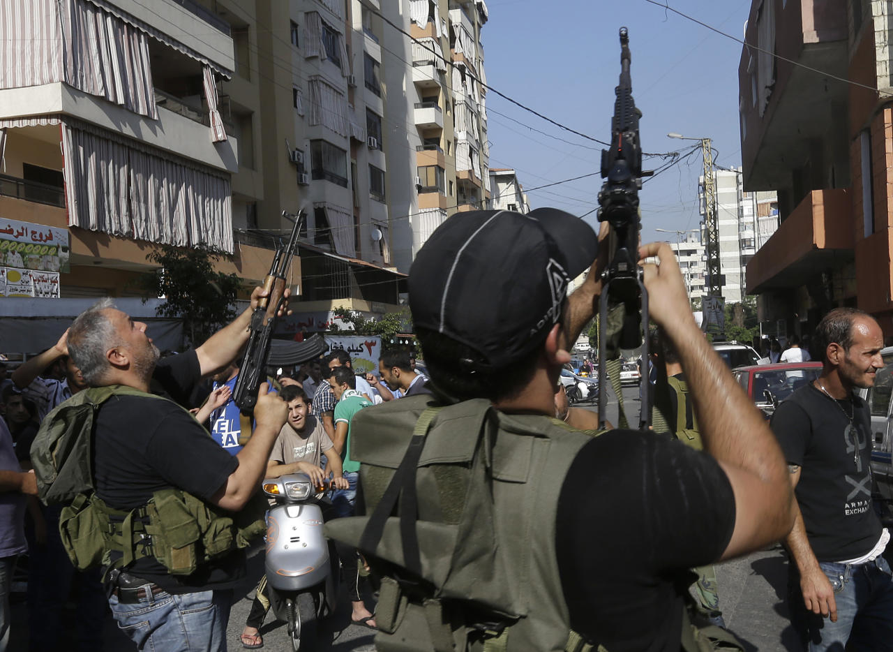 Lebanese Shiite gunmen fire their AK-47 during the funeral procession of Hamad al-Mekdad, 42, who was killed on Thursday by a car bomb explosion, during his funeral procession at an predominantly Shiite area and stronghold of the Lebanese militant group Hezbollah in the southern suburb of Beirut, Lebanon, Friday, Aug. 16, 2013. Lebanese forensic experts collected evidence Friday at the scene of a massive explosion in a southern suburb of Beirut that killed dozens of people and wounded hundreds, the deadliest blast in the area in nearly three decades. (AP Photo/Hussein Malla)