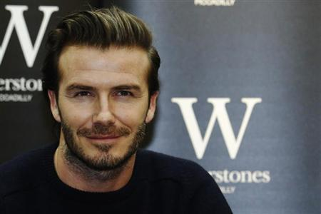 """Retired soccer player David Beckham poses with his book """"David Beckham"""" at a bookshop in London"""