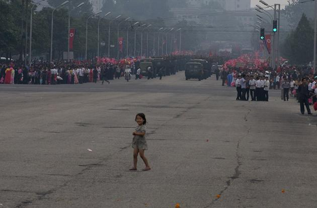 A girl walks into the street after a military parade. North Korea the largest army in the world per capita at 1.1 million active soldiers and 8.2 million in the reserves. This means 47 percent of the population is either active military or in the reserves. In America, the number is 1.4 percent.