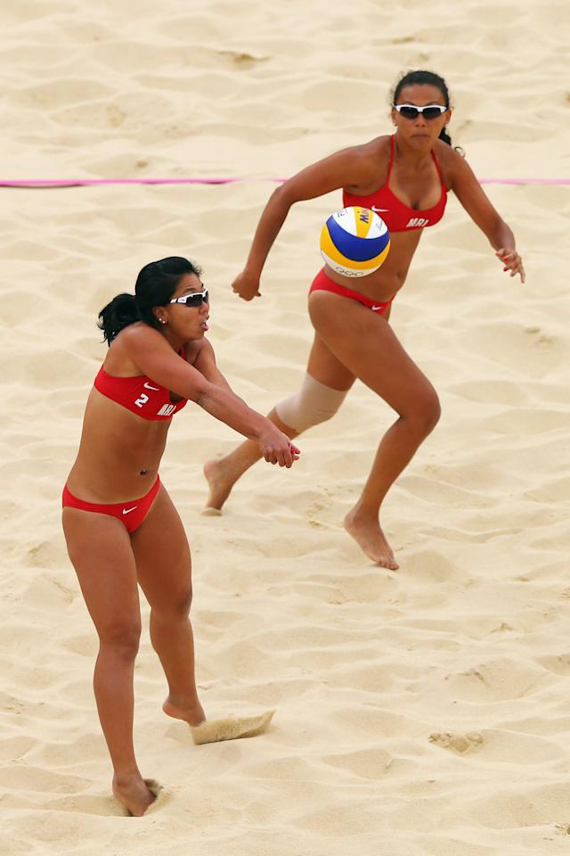 LONDON, ENGLAND - JULY 28:  Natacha Rigobert looks on while Nioun Chin Elodie Li Yuk Lo of Mauritius (L) returns the ball during the Women's Beach Volleyball Preliminary Round on Day 1 of the London 2012 Olympic Games at Horse Guards Parade on July 28, 2012 in London, England.  (Photo by Ryan Pierse/Getty Images)