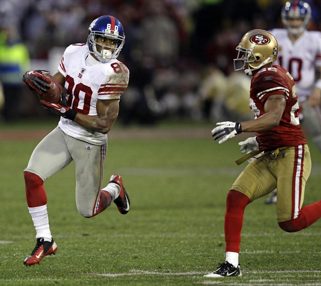 New York Giants' Victor Cruz (80) catches a pass in front of San Francisco 49ers' Carlos Rogers (22) during the first half of the NFC Championship NFL football game Sunday, Jan. 22, 2012, in San Francisco. (AP Photo/David J. Phillip)