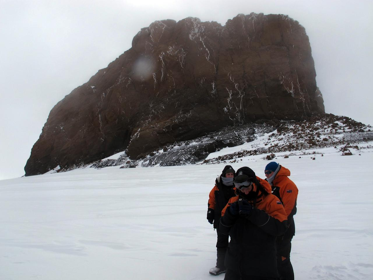 "This Jan. 20, 2013 photo shows tourists near Castle Rock on Crater Hill on Ross Island, Antarctica. Tourism is rebounding here five years after the financial crisis stifled what had been a burgeoning industry. And it's not just retirees watching penguins from the deck of a ship. Visitors are taking tours inland and even engaging in ""adventure tourism"" like skydiving and scuba diving under the ever-sunlit skies of a Southern Hemisphere summer. (AP Photo/Rod McGuirk)"