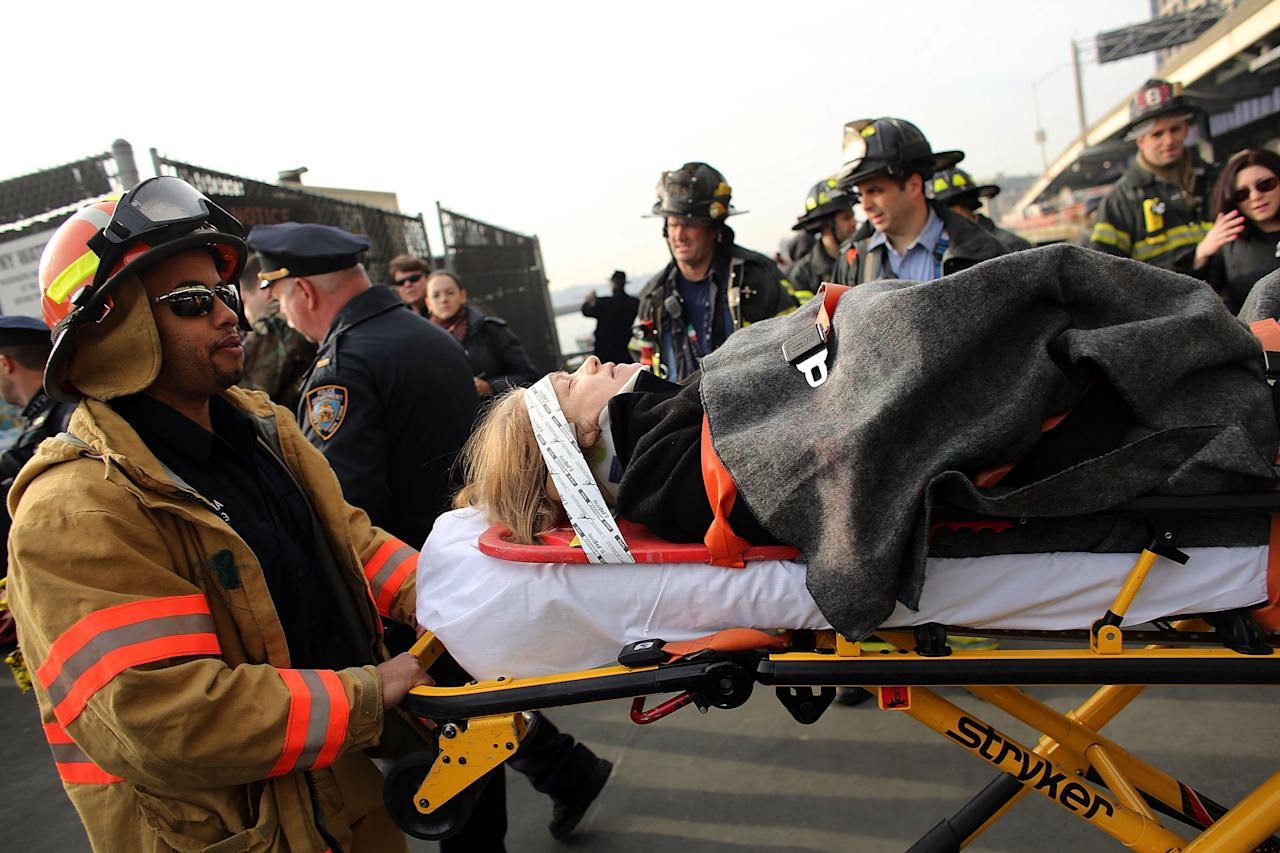 An injured woman is carried to a waiting ambulance following an early morning ferry accident during rush hour in Lower Manhattan on January 9, 2013 in New York City. About 50 people were injured in the accident, which left a large gash on the front side of the Seastreak ferry at Pier 11.  (Photo by Spencer Platt/Getty Images)