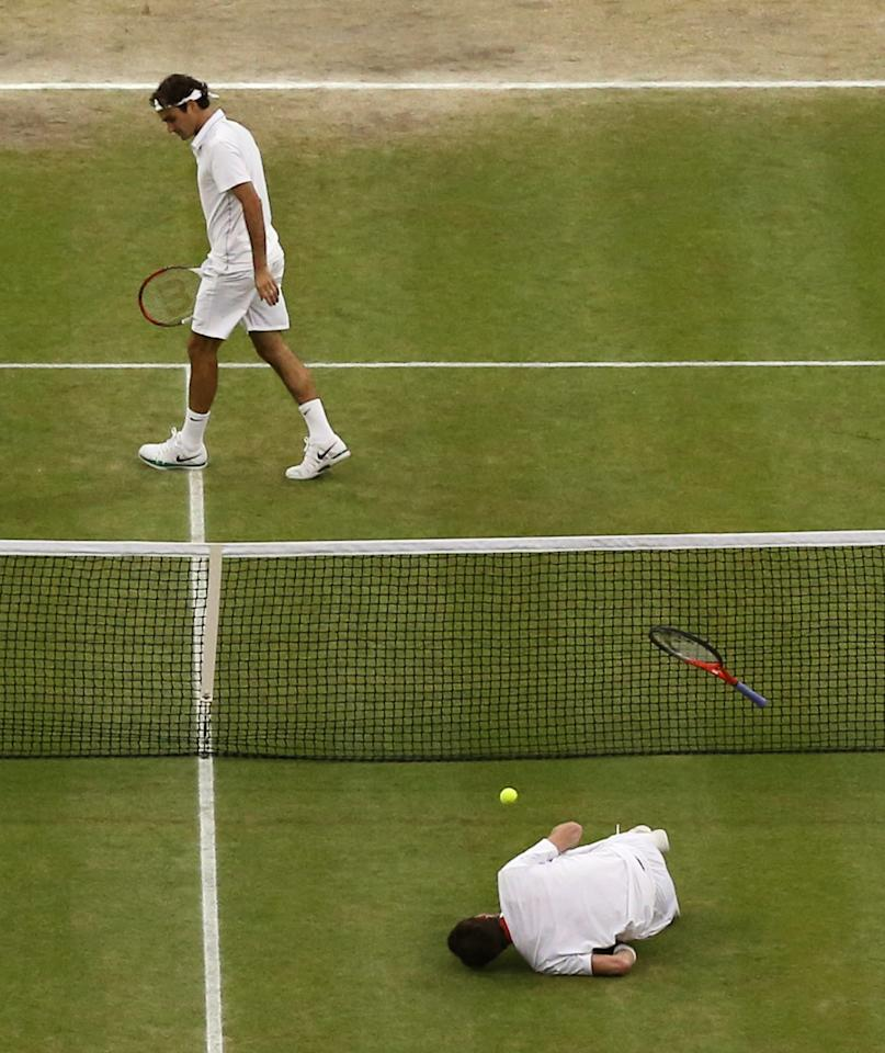 Andy Murray of Britain, front, takes a fall during the men's singles final match against Roger Federer of Switzerland at the All England Lawn Tennis Championships at Wimbledon, England, Sunday, July 8, 2012. (AP Photo/Clive Rose, Pool)