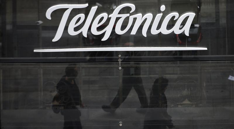 People are reflected as they walk past Spanish telecom group Telefonica's flagship store in central Madrid