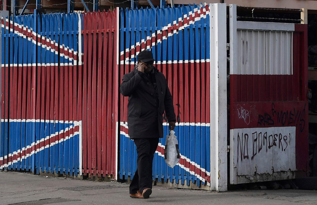 "A man walks past fencing and gates painted in the colours of the British union flag and the English flag of St. George with graffiti reading ""No borders"" written on it in east London, Britain, February 18, 2017. REUTERS/Toby Melville"
