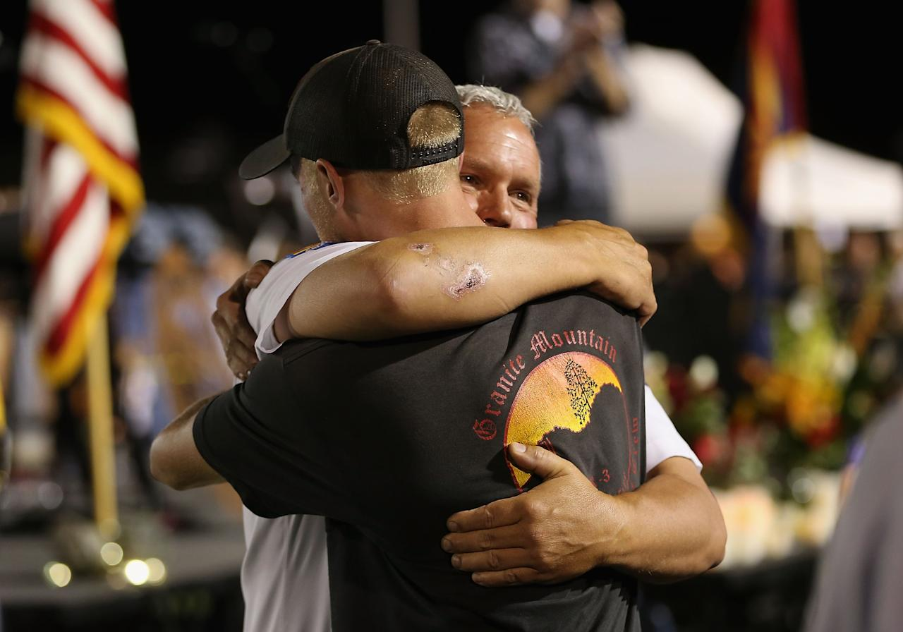 PRESCOTT, AZ - JULY 02: Prescott Fire Marshal Division Chief, Don Devendorf hugs firefighter Brendan McDonough, the lone survivor of the Granite Mountain Hotshot crew, as they leave the candlelight vigil in honor of the 19 fallen firefighters at Prescott High School on July 2, 2013 in Prescott, Arizona. 19 Granite Mountain Interagency Hotshot Crew firefighters died battling a fast-moving wildfire near Yarnell, AZ on Sunday. (Photo by Christian Petersen/Getty Images)
