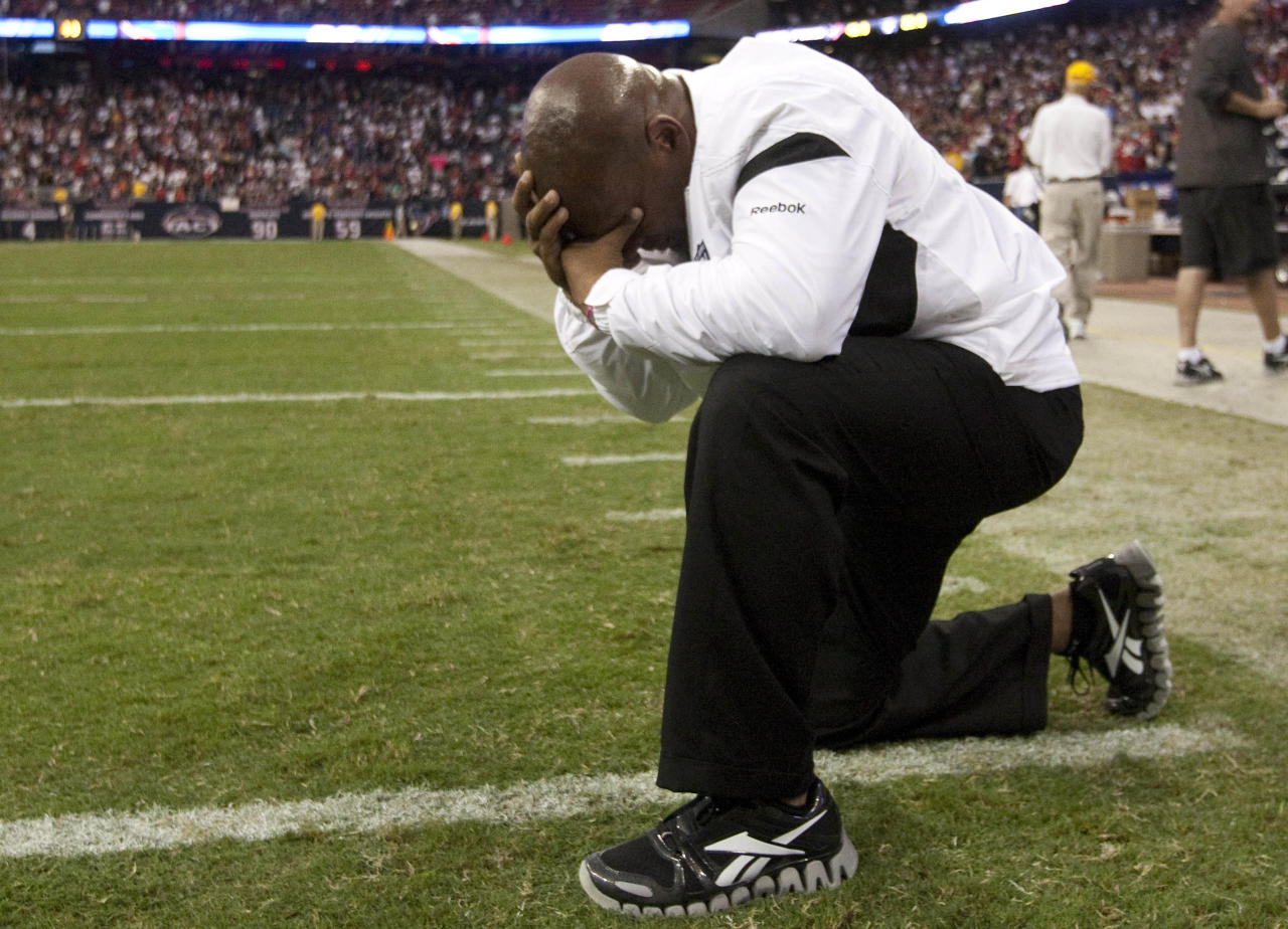 Oakland Raiders head coach Hue Jackson kneels on the field after a 25-20 victory over the Houston Texans in an NFL football game Sunday, Oct. 9, 2011, in Houston. (AP Photo/Houston Chronicle, Brett Coomer) MANDATORY CREDIT