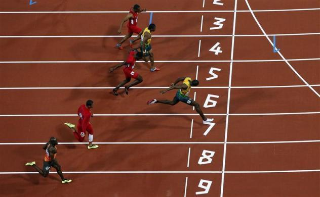 Jamaica's Usain Bolt (R) crosses the finish line to win the men's 100m final during the London 2012 Olympic Games at the Olympic Stadium August 5, 2012.