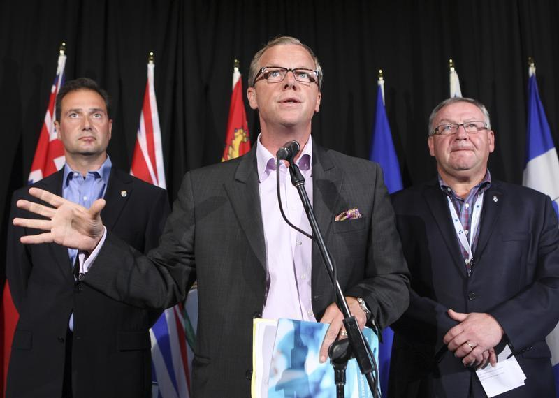 Saskatchewan Premier Brad Wall (C), flanked by P.E.I Premier Robert Ghiz (L) and Nova Scotia Premier Darrell Dexter (R), present the first report of the health care innovation working group.