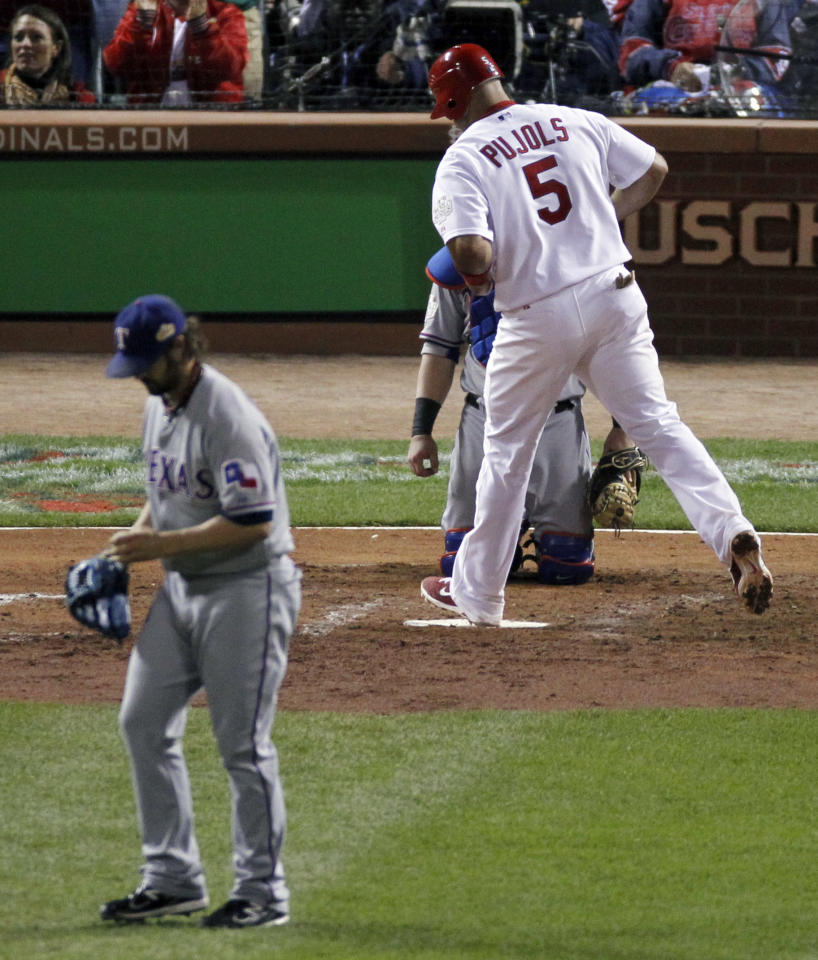 St. Louis Cardinals' Albert Pujols scores after Texas Rangers pitcher C.J. Wilson hit the Cardinals' Rafael Furcal with a pitch while the bases were loaded during the fifth inning of Game 7 of baseball's World Series Friday, Oct. 28, 2011, in St. Louis. Texas Rangers' Mike Napoli catches. (AP Photo/Jeff Roberson)
