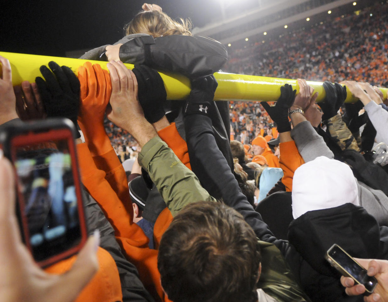 Oklahoma State fans carry a goal post they tore down following the Cowboy's 44-10 win of rival Oklahoma in an NCAA college football game in Stillwater, Okla., Saturday, Dec. 3, 2011. (AP Photo/Brody Schmidt)