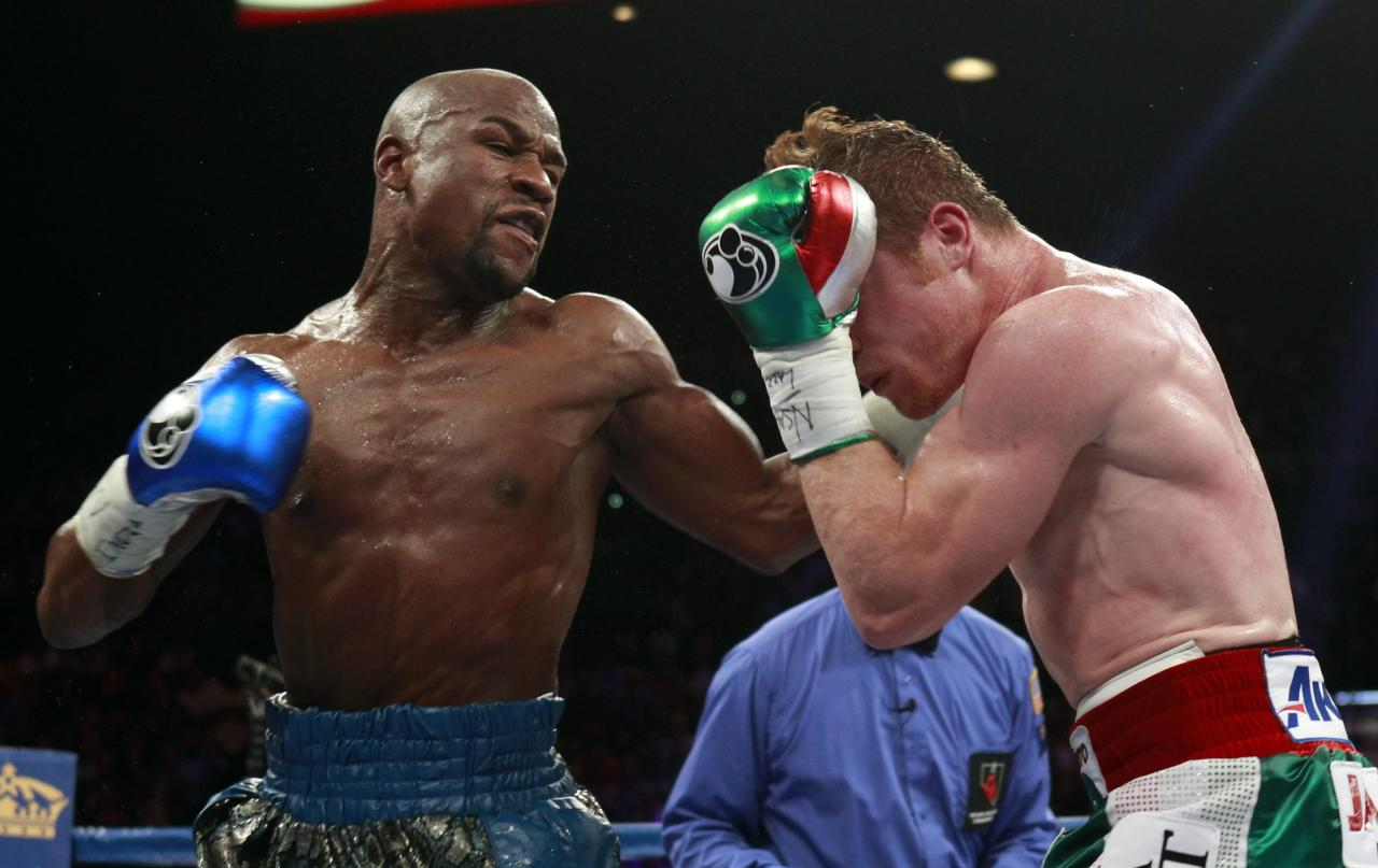 Floyd Mayweather Jr. (L) of the U.S. punches at WBC/WBA 154-pound champion Canelo Alvarez during their title fight at the MGM Grand Garden Arena in Las Vegas, Nevada, September 14, 2013. REUTERS/Steve Marcus (UNITED STATES - Tags: SPORT BOXING)