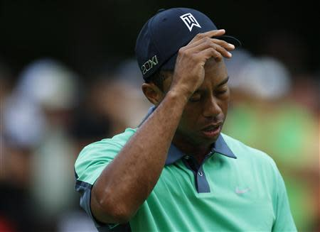 Woods of the U.S. walks off the course after finishing the first round of the BMW Championship golf tournament in Lake Forest