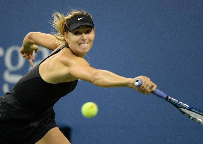 Maria Sharapova of Russia hits a return to Sabine Lisicki of Germany during their US Open 2014 women's singles match at the USTA Billie Jean King National Center August 29, 2014 in New York