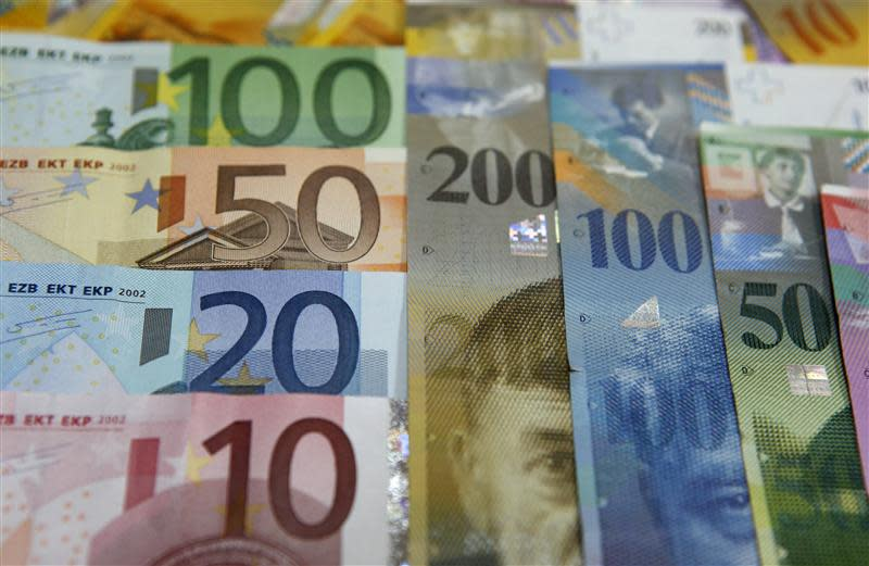 File photo illustration of various Euro banknotes lying next to various Swiss Franc banknotes