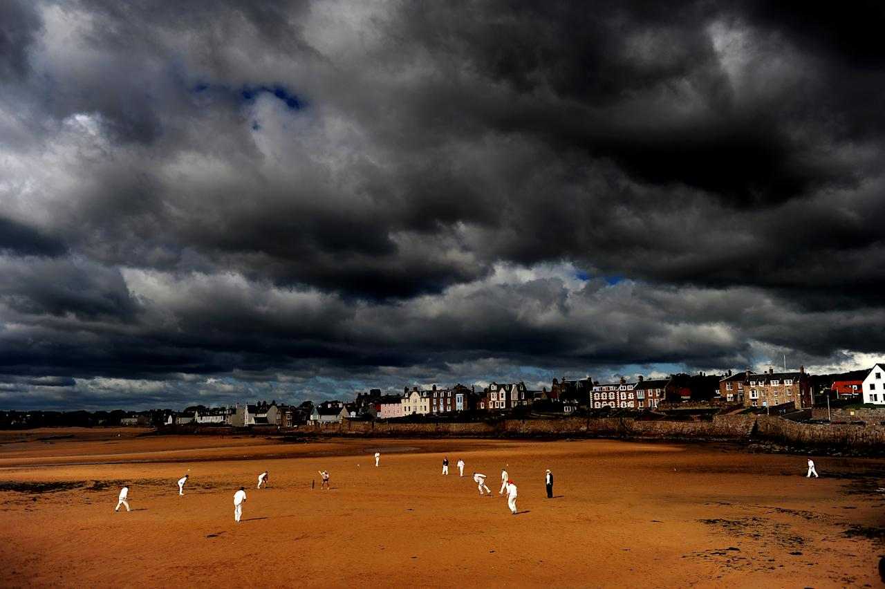 FIFE, SCOTLAND - AUGUST 29: (EDITORS NOTE: A [graduated] color filter was used for this image.) Cricketers from the Ship Inn Cricket Club play on the beach on August 29, 2010 in Elie, Scotland.  (Photo by Laurence Griffiths/Getty Images)
