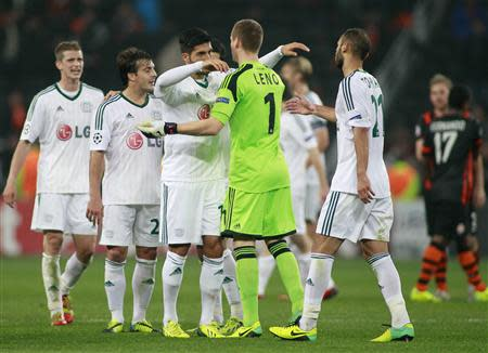 Bayer Leverkusen's players greet each other after their Champions League soccer match against Shakhtar Donetsk at the Donbass Arena stadium in Donetsk