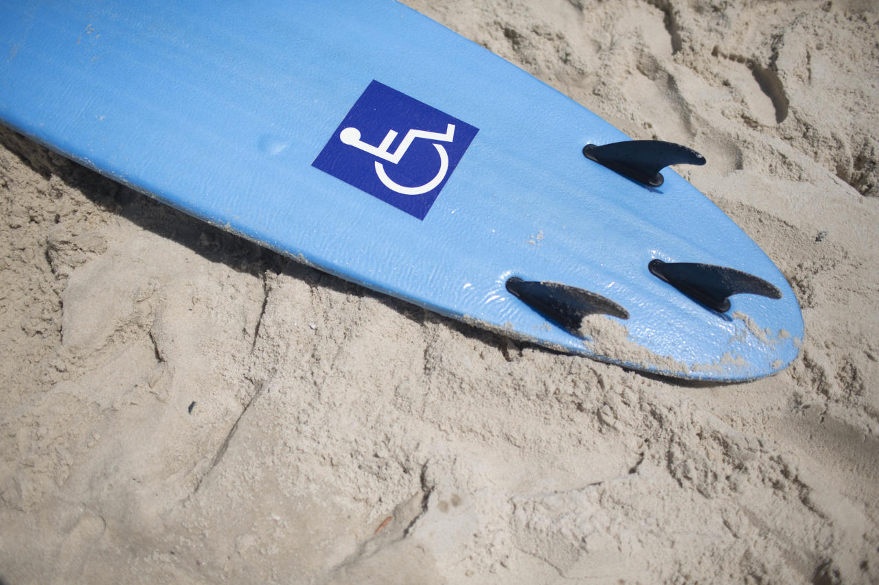 In this March 10, 2013 photo, a surfboard tagged with a disabled symbol sits on the sand in Leblon beach in Rio de Janeiro, Brazil. Dozens of disabled people on this special strip of Rio de Janeiro beach are conquering the waves. Men and women with cerebral palsy, Down syndrome, people missing a limb, the blind, the deaf and even the paralyzed all hit the waves at Leblon. They all require a different kind of assistance depending on their disabilities and maneuver their boards in different ways - some standing, some on their knees, others flat on their bellies and using their body weight to steer the boards. (AP Photo/Felipe Dana)
