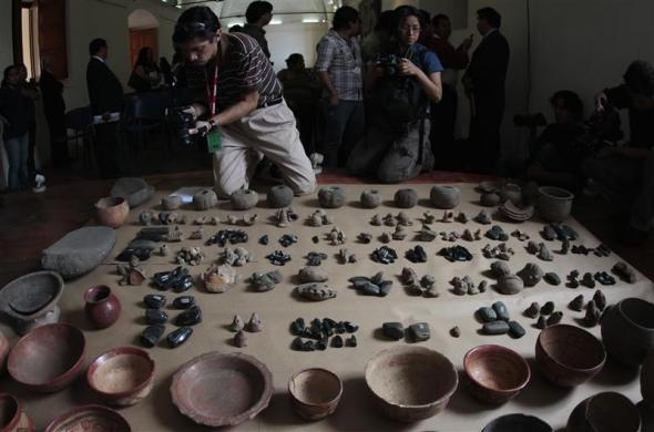 Members of the media take pictures of archeological pieces are presented by the Guatemalan Authorities in Guatemala City June 13, 2012. According to the authorities, 440 archeological pieces were recovered in 2008 after they were sold to an antique store in Chichicastenango, in the Quiche region, north of the country.