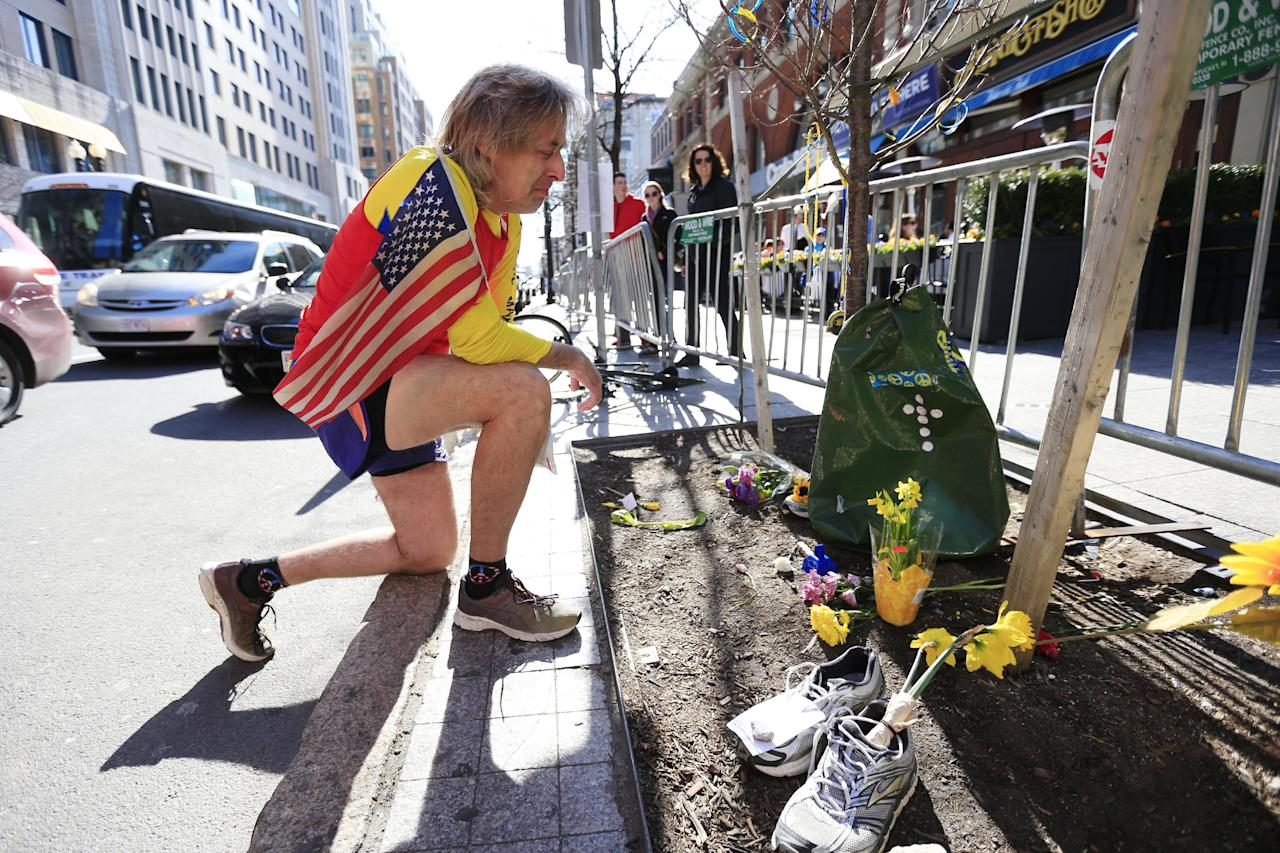 Ron McCracken of Dallas pays his respects at a makeshift memorial honoring to the victims of the 2013 Boston Marathon bombings ahead of Monday's 118th Boston Marathon, Sunday, April 20, 2014, in Boston. McCracken's race last year was cut short due to bombings and Monday's race will mark his 14th year running in the Boston Marathon. The memorial is where the second of two explosions happened last year near the finish line. (AP Photo/Matt Rourke)