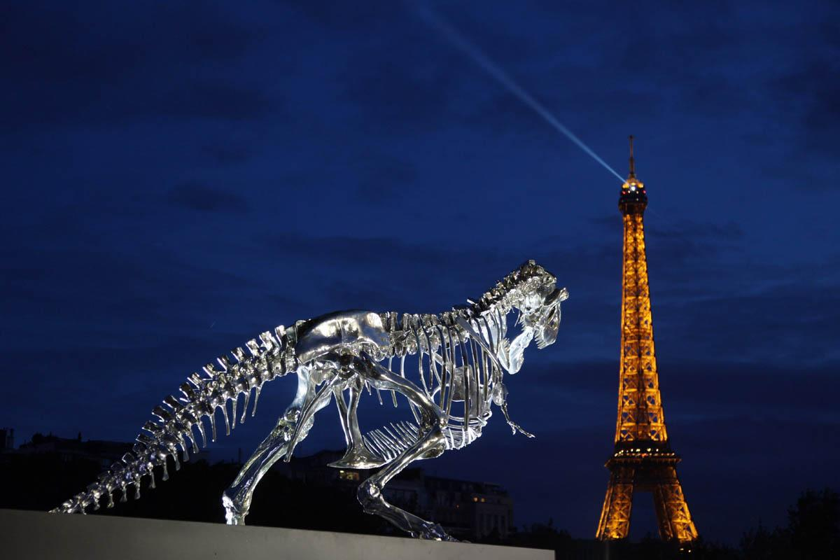 A giant chrome brushed aluminium skeleton of a Tyrannosaurus (T-Rex) dinosaur (L), made by French sculptor and painter Philippe Pasqua, stands at the pier of riverboat company Bateaux-Mouches on June 12, 2013 in Paris, with the Eiffel tower in the background (R). AFP PHOTO / CLAIRE LEBERTRE