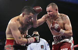 Mike Alvarado, right, exchanges punches with Brandon Rios during a WBO super lightweight title fight last year. (AP)