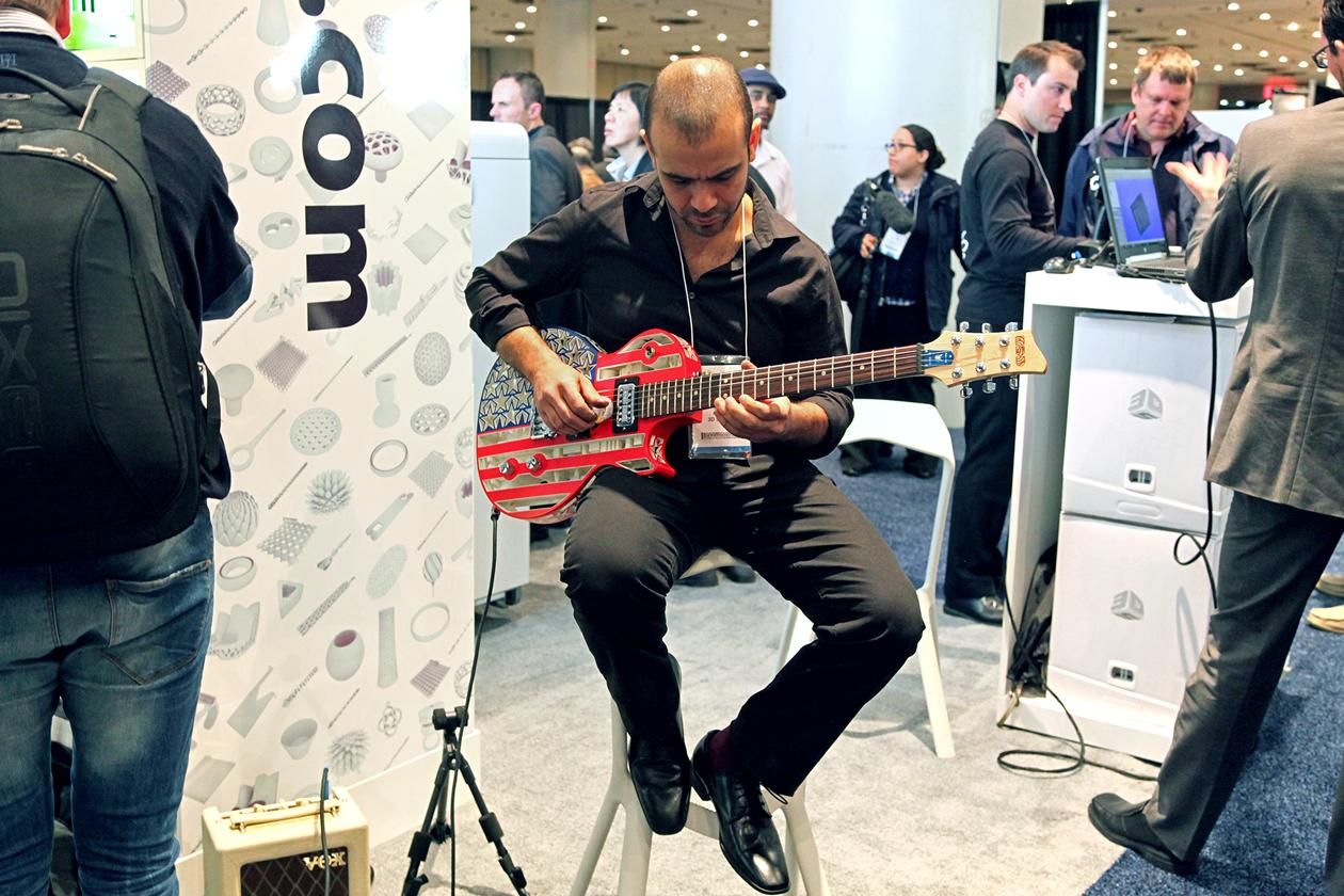 "An employee of <a target=""_blank"" href=""http://www.3dsystems.com/"">3D Systems</a> playing with a guitar that was constructed with parts created with 3D printers."